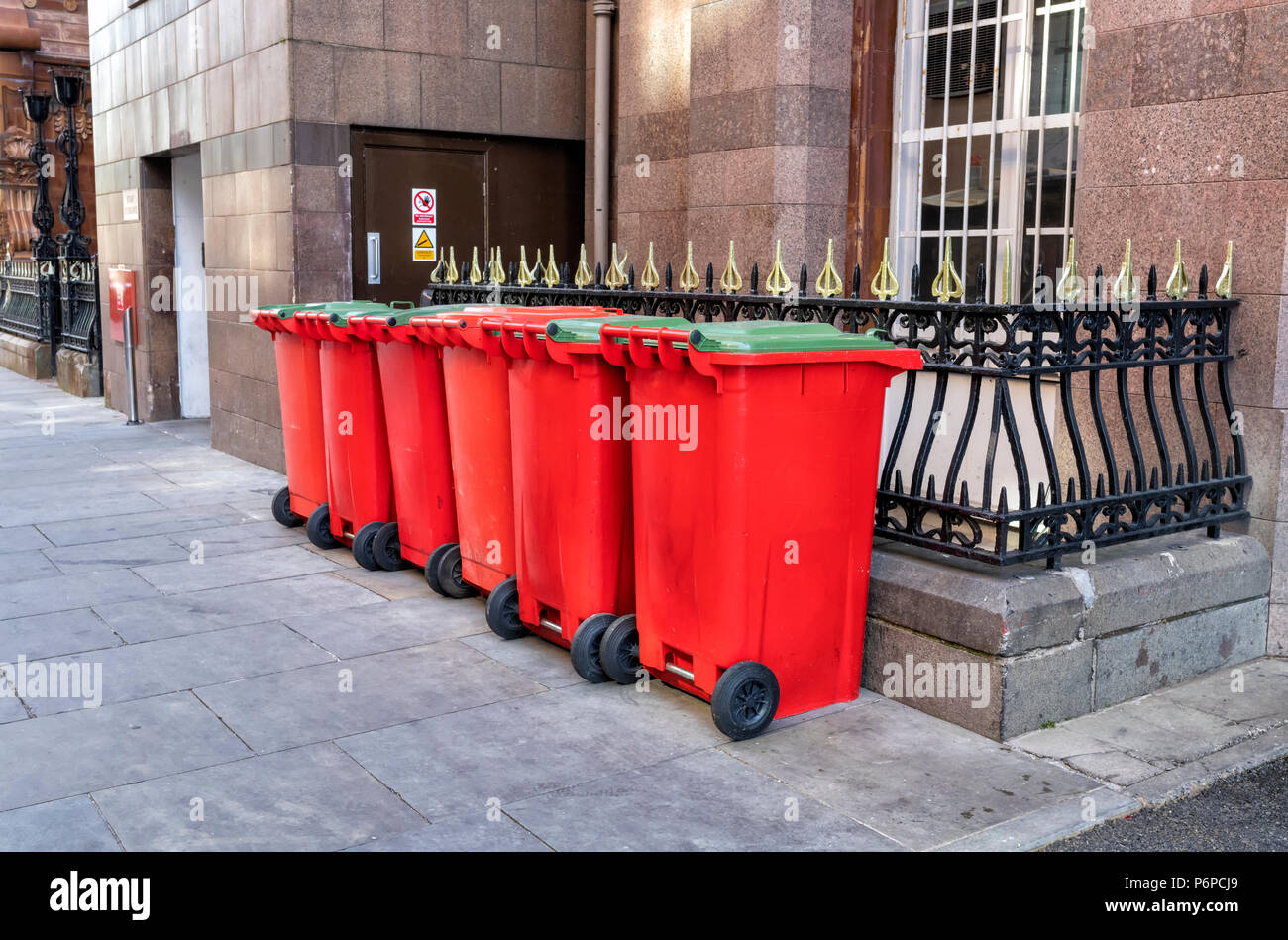 A row of 6 red and 5 green wheelie bins on the pavement in a street in Manchester City Centre, UK - Stock Image