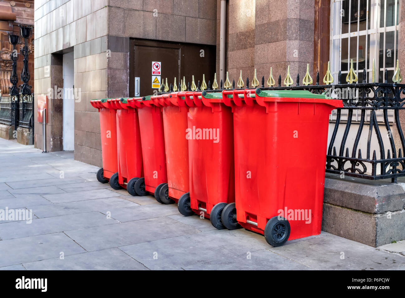 A row of 6 red wheelie bins on the pavement in a street in Manchester City Centre, UK - Stock Image