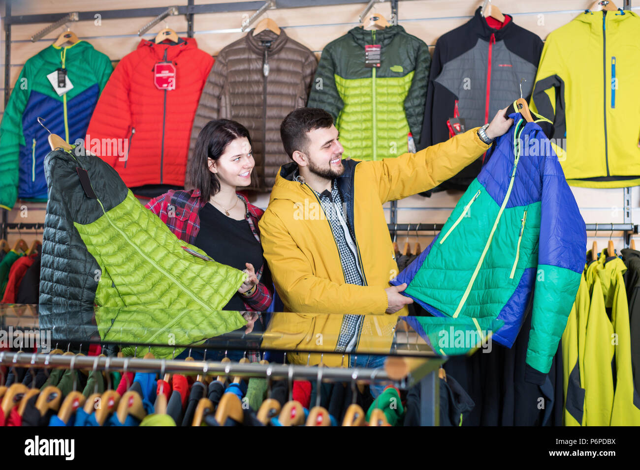 11db9a6bf2 Young loving couple choosing on windcheater in sports clothes shop ...