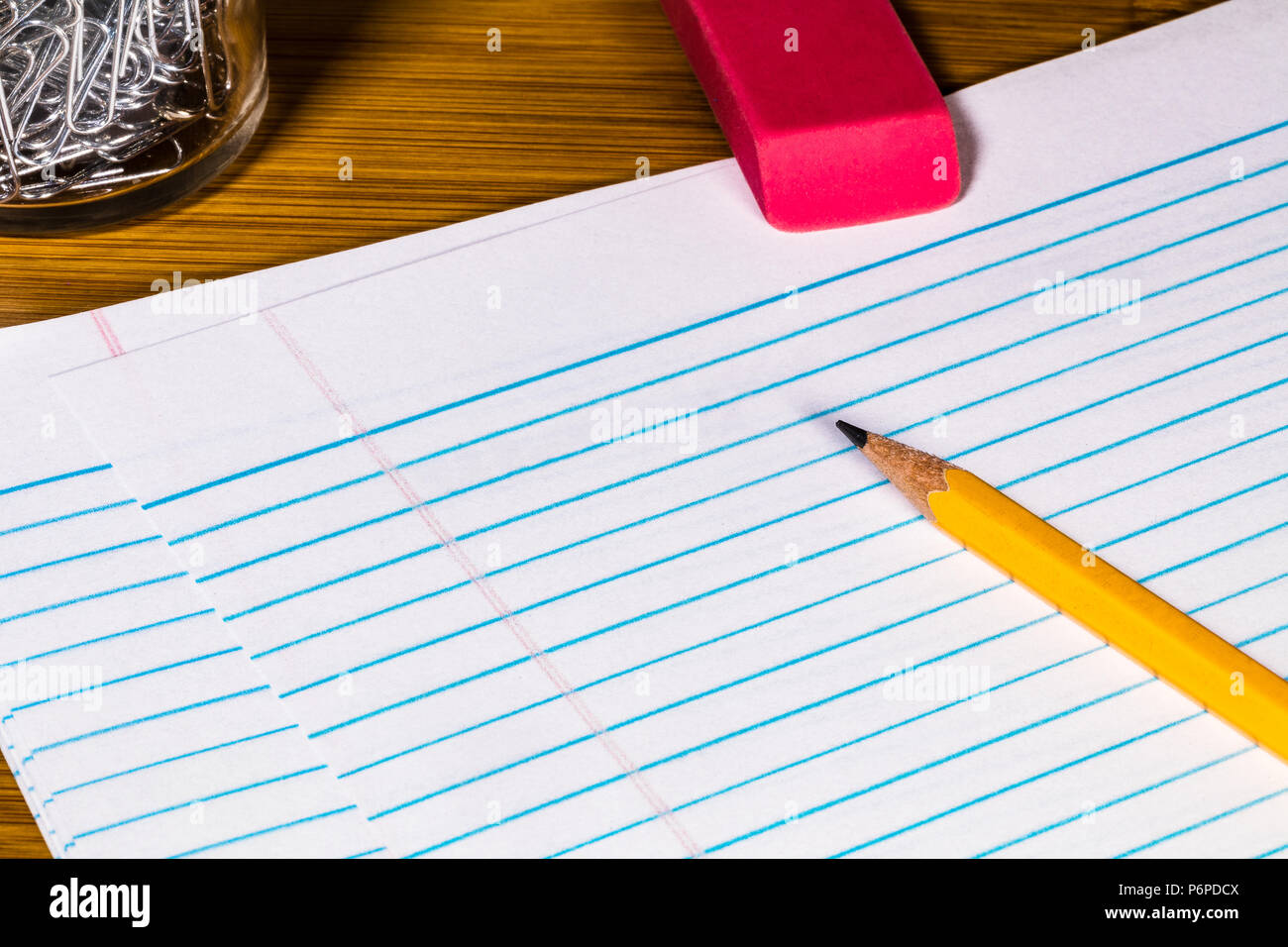 a #2 Pencil, Eraser, paper clips and Filler paper with plenty of room for Copy.  Several sheets of filler paper are featherd below. - Stock Image