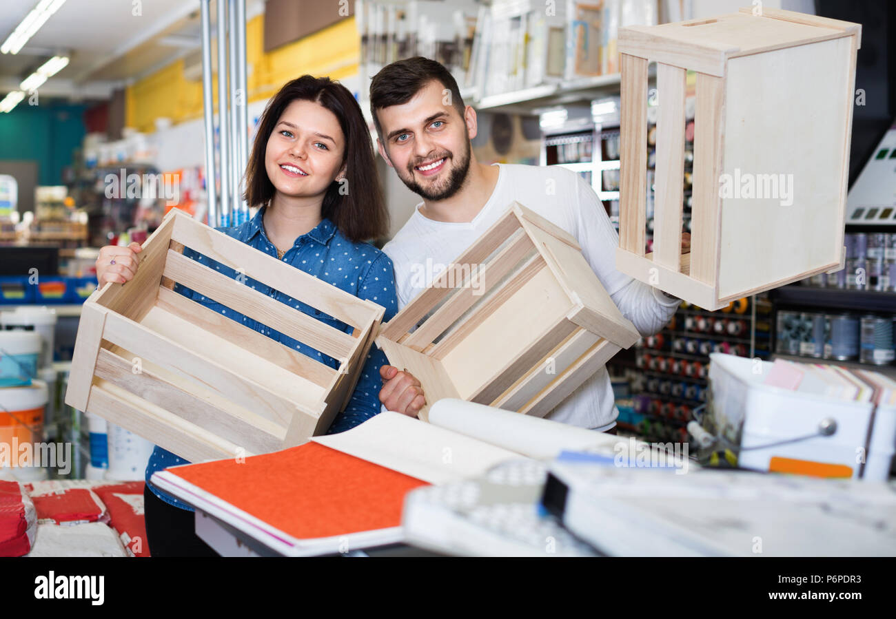 Smiling happy couple purchasing decorative boxes for house