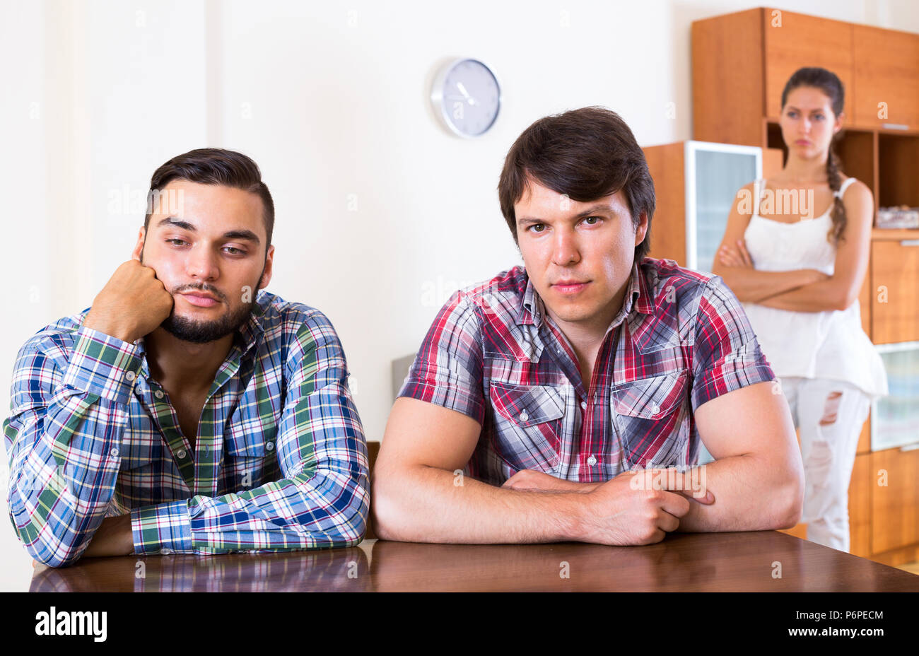 Portrait of sad young adults at home: problems of love triangle - Stock Image