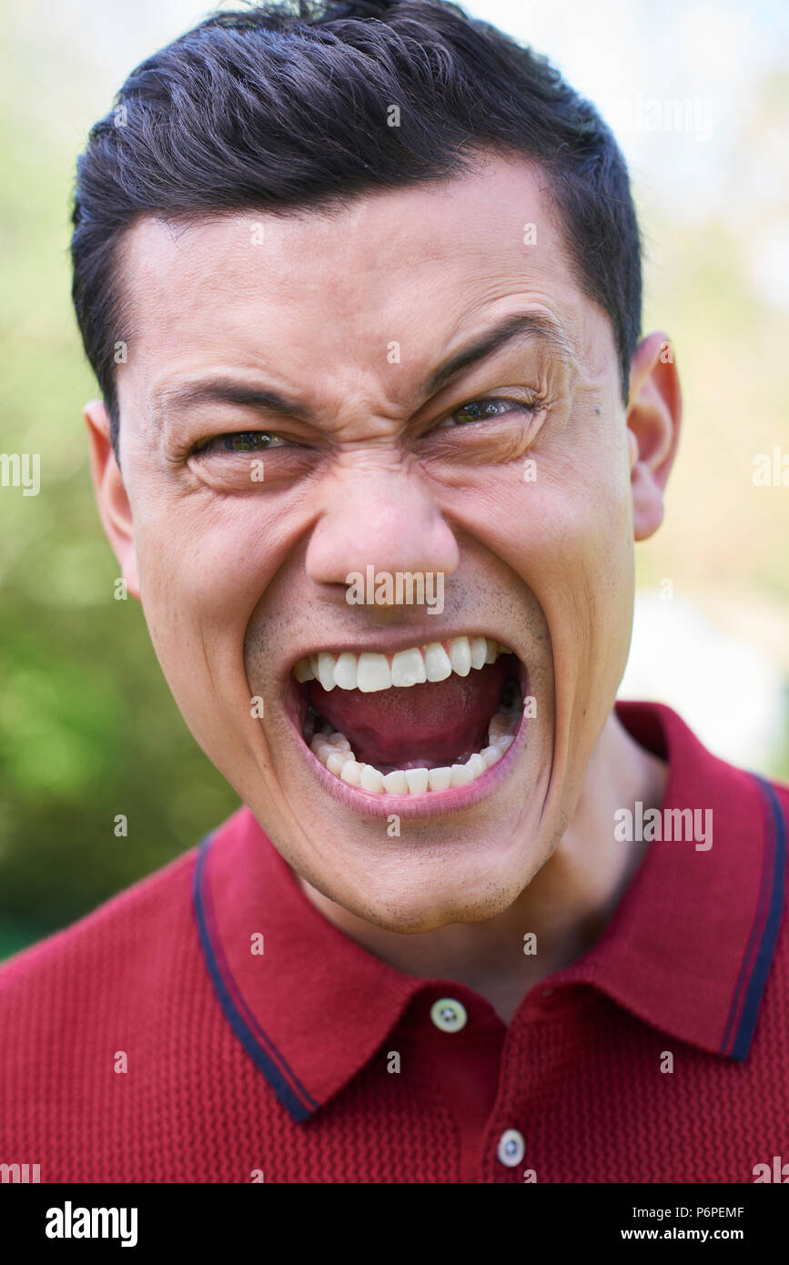 Outdoor Shot Of Angry Young Man Shouting At Camera - Stock Image