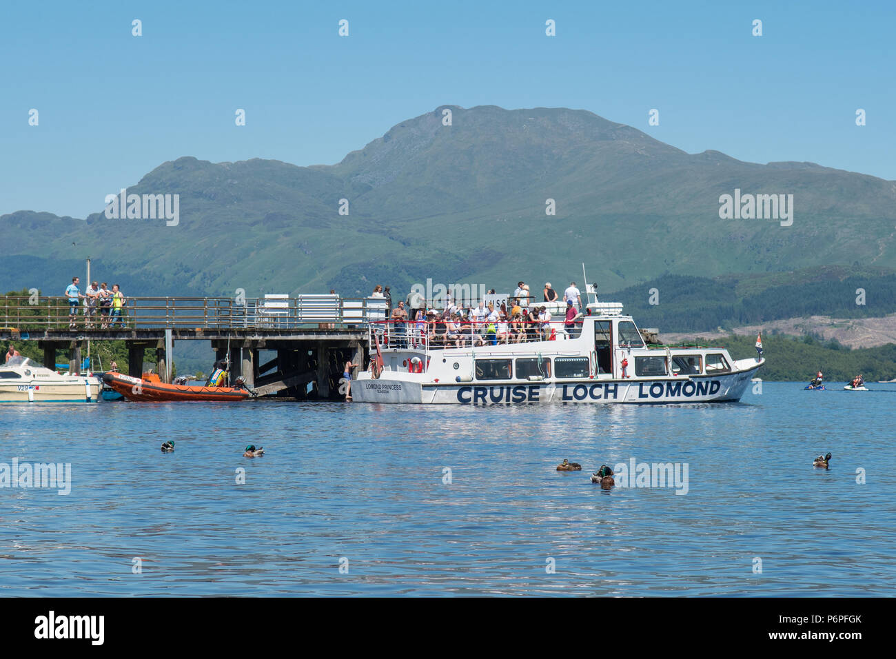 Loch Lomond - Luss Pier on a hot summer day with Ben Lomond behind, with Cruise Boat  picking up passengers, Scotland, UK - Stock Image