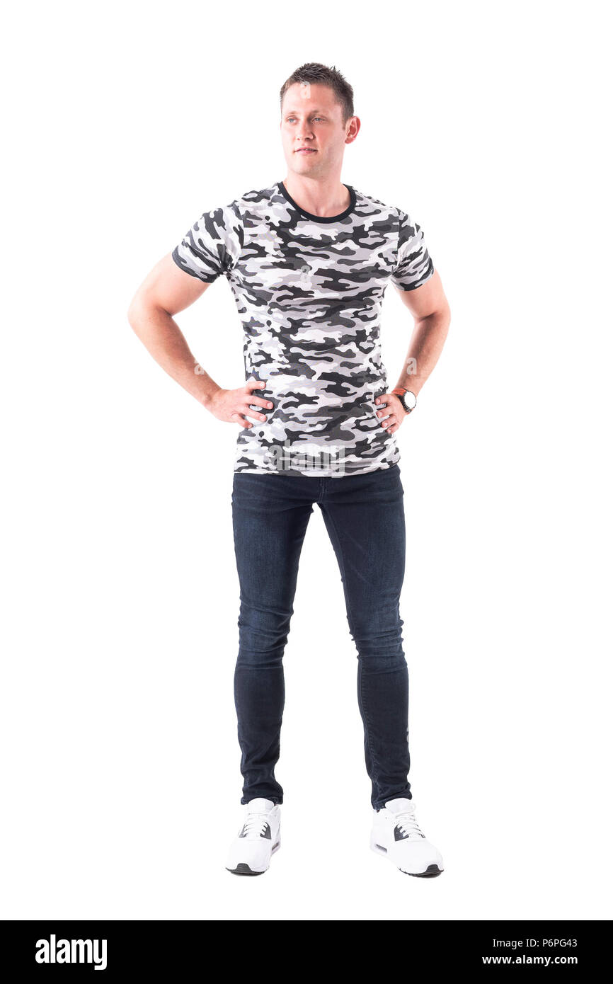 Confident successful young adult man in camouflage t-shirt with hands on hips looking away. Full body isolated on white background. - Stock Image