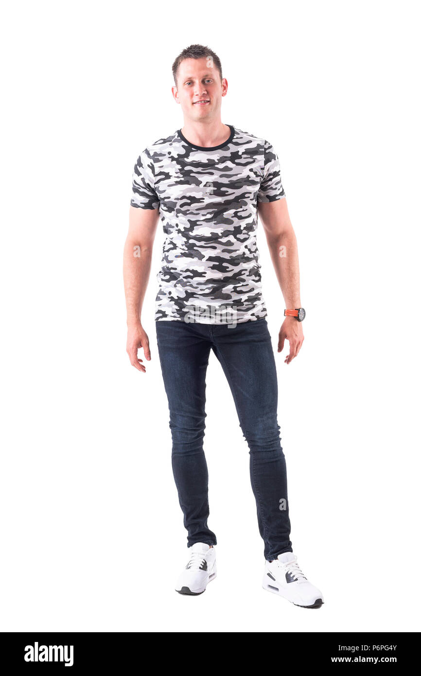 Relaxed happy smiling young adult in army camouflage t-shirt looking at camera. Full body isolated on white background. - Stock Image