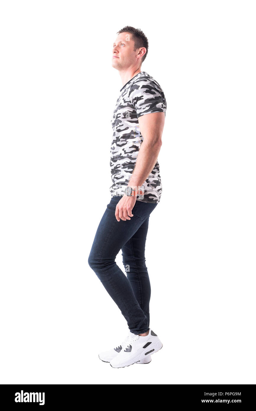 Handsome fit man in army pattern t-shirt walking and looking up. Side view. Full body isolated on white background. - Stock Image