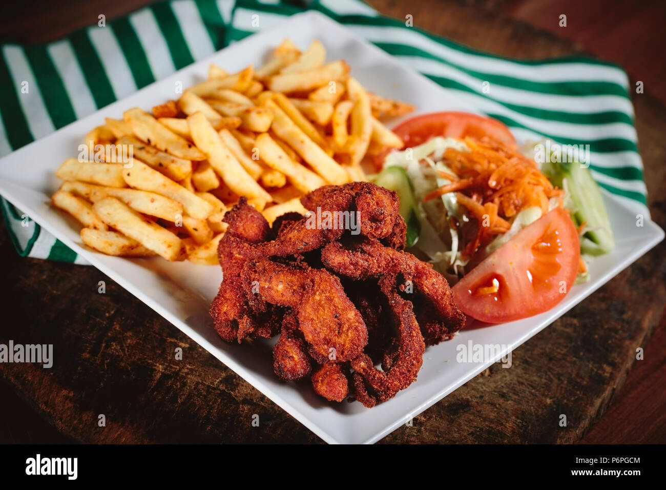 Fried chicken with cajun spices and potatoes - Stock Image
