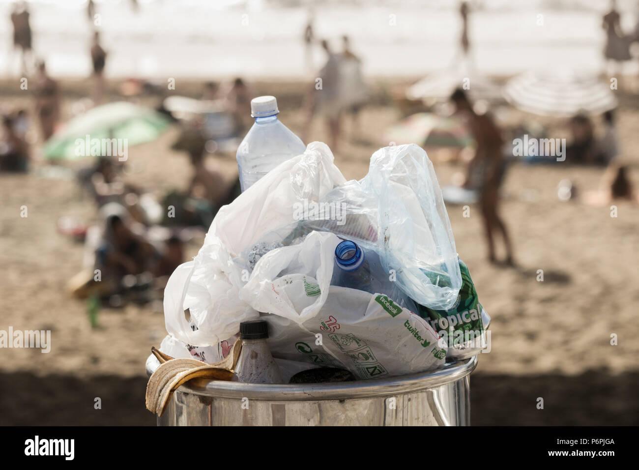 Overflowing litter bin full of plastic bottles and plastic bags on beach Stock Photo