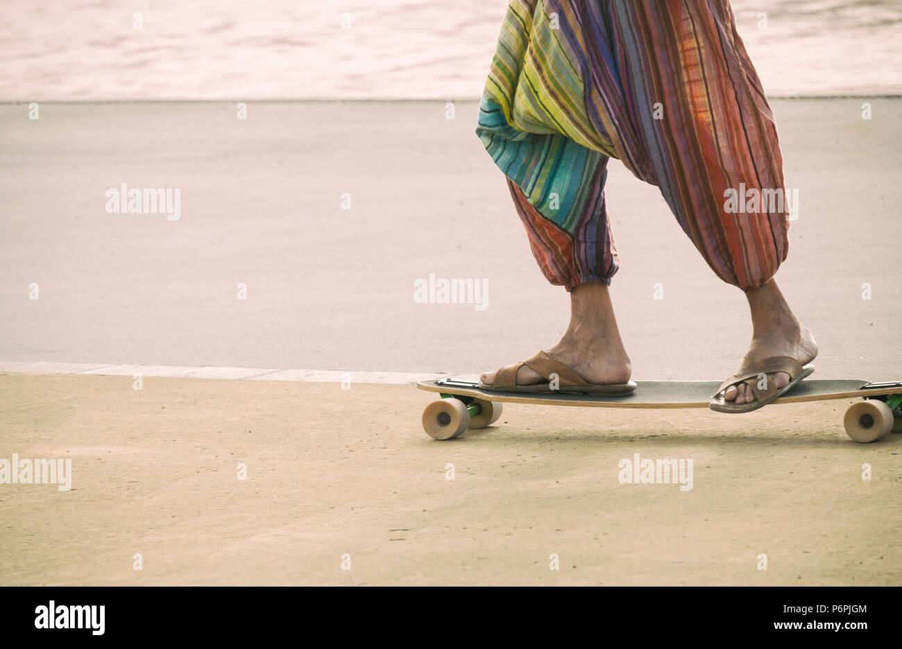 Hippy riding a skateboard wearing Flip Flops/sandals. - Stock Image