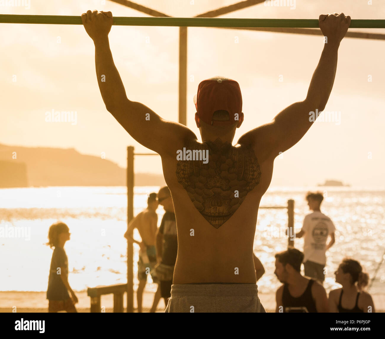 Rear view of muscular man with back tattoo doing pull ups/chin ups on beach in Spain - Stock Image