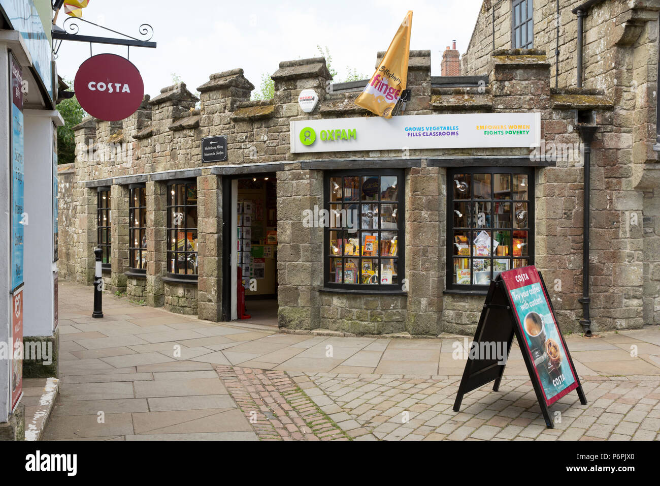An Oxfam shop nex to a Costa Coffe shop in Shaftesbury North Dorset England UK GB - Stock Image