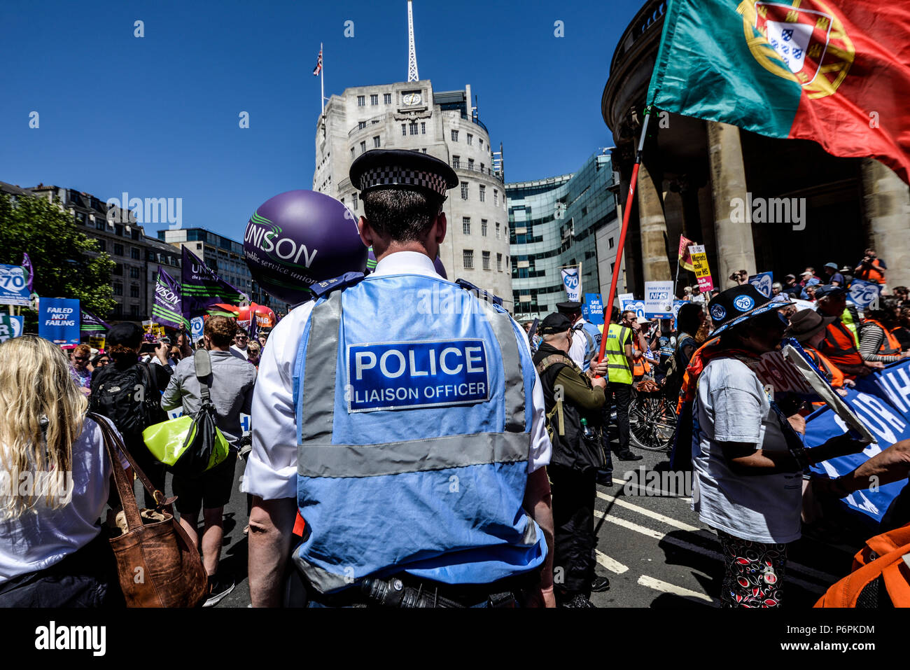 Police liaison officer in London, UK, with crowds of demonstrators. People. British police. NHS70 march - Stock Image