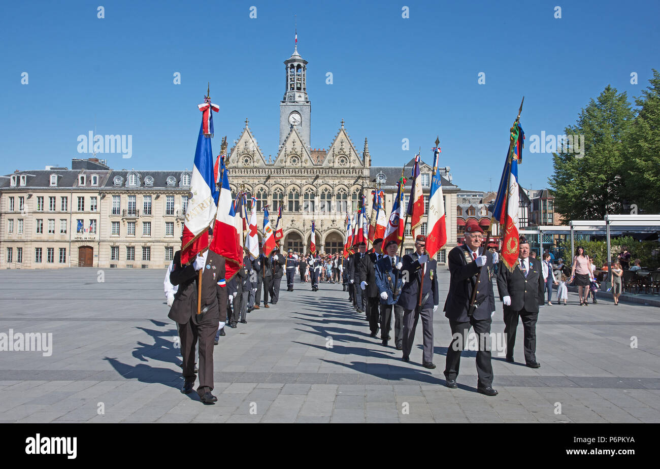 Men marching with raised banners and flags for Victory In Europe VE day 8th May 2018 in Place de l'Hotel de Ville St Quentin, Aisne, France. Stock Photo