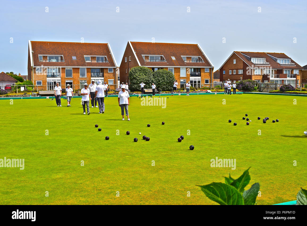 Players enjoying a quiet game of bowls at Milford on Sea Bowls Club in the Summer sunshine. Hampshire - Stock Image