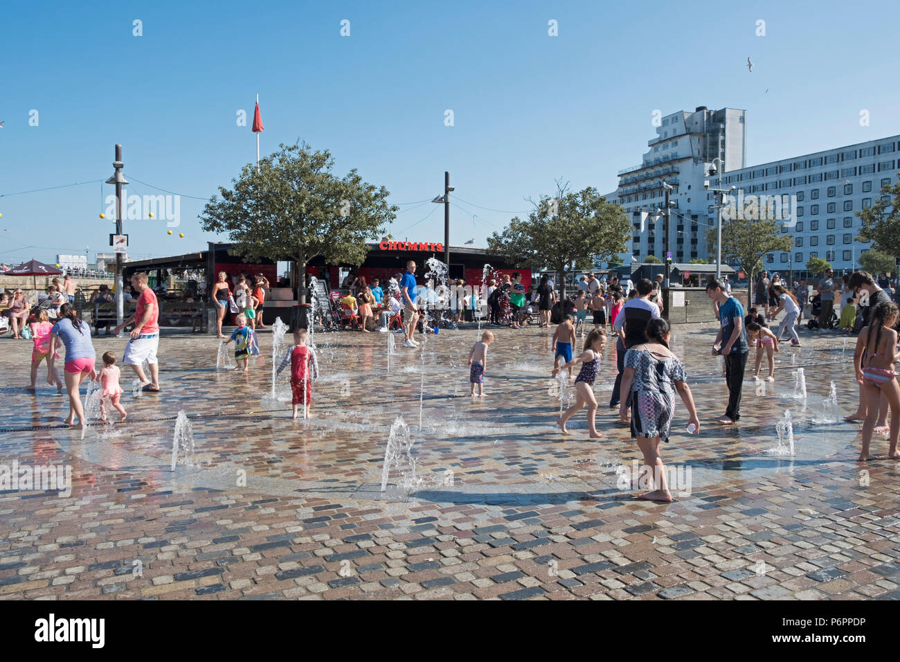 Children playing in the water spout fountains at Folkestone Harbour, Kent, UK - Stock Image
