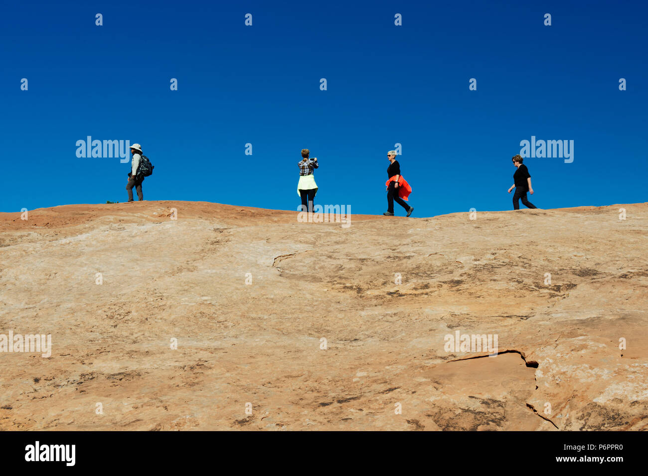 Four female hikers walking and taking pictures on Upheaval Dome Overlook trail, Canyonland National Park, Utah, USA. - Stock Image