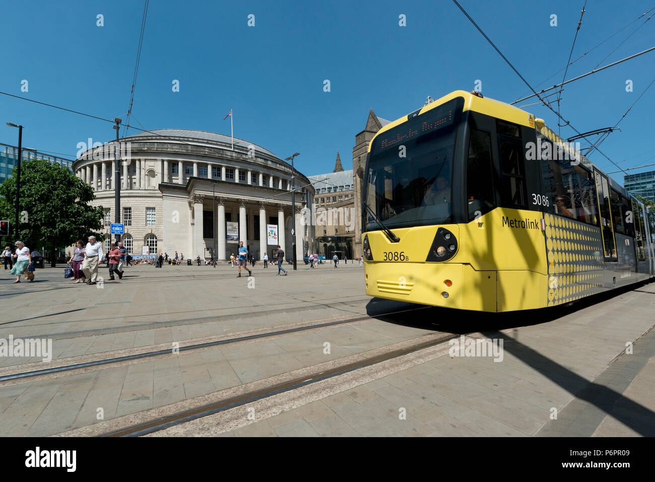 A Metrolink tram passes infront of the Central Library in St Peter's Sqaure in Manchester. - Stock Image