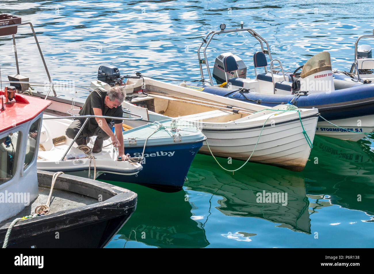 Burtonport, County Donegal, Ireland weather. 2nd July 2018. The warm weather continues with a cooling breeze in the harbour on Ireland's north-west coast. A man takes advantage of the hot day to fix his boat. Credit: Richard Wayman/Alamy Live News - Stock Image