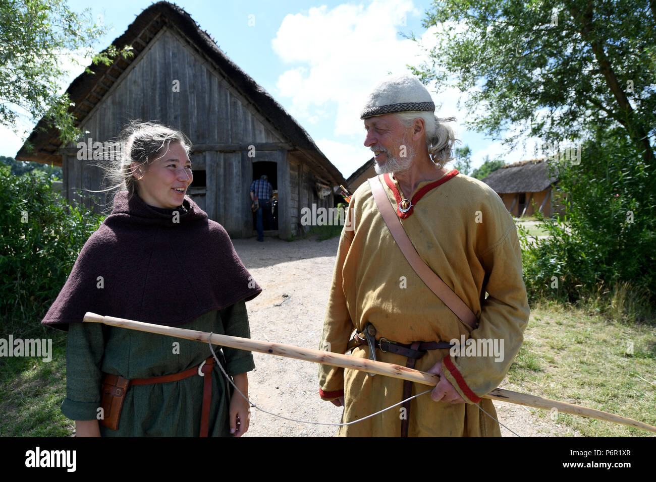 19.06.2018, Schleswig-Holstein, Busdorf: employees in authentic Viking clothing stand on the grounds of the Viking houses of Haithabu. The UNESCO World Heritage Kowithee will decide on the inclusion of new monuments in the World Heritage List at its meeting in Bahrain from 24 June to 3 July. From Germany are Viking-time Statten in Danewerk and Haithabu in Schleswig here. (to dpa 'Wikingestatten as a World Heritage:' Then we play World League ') Photo: Carsten Rehder/dpa | usage worldwide - Stock Image