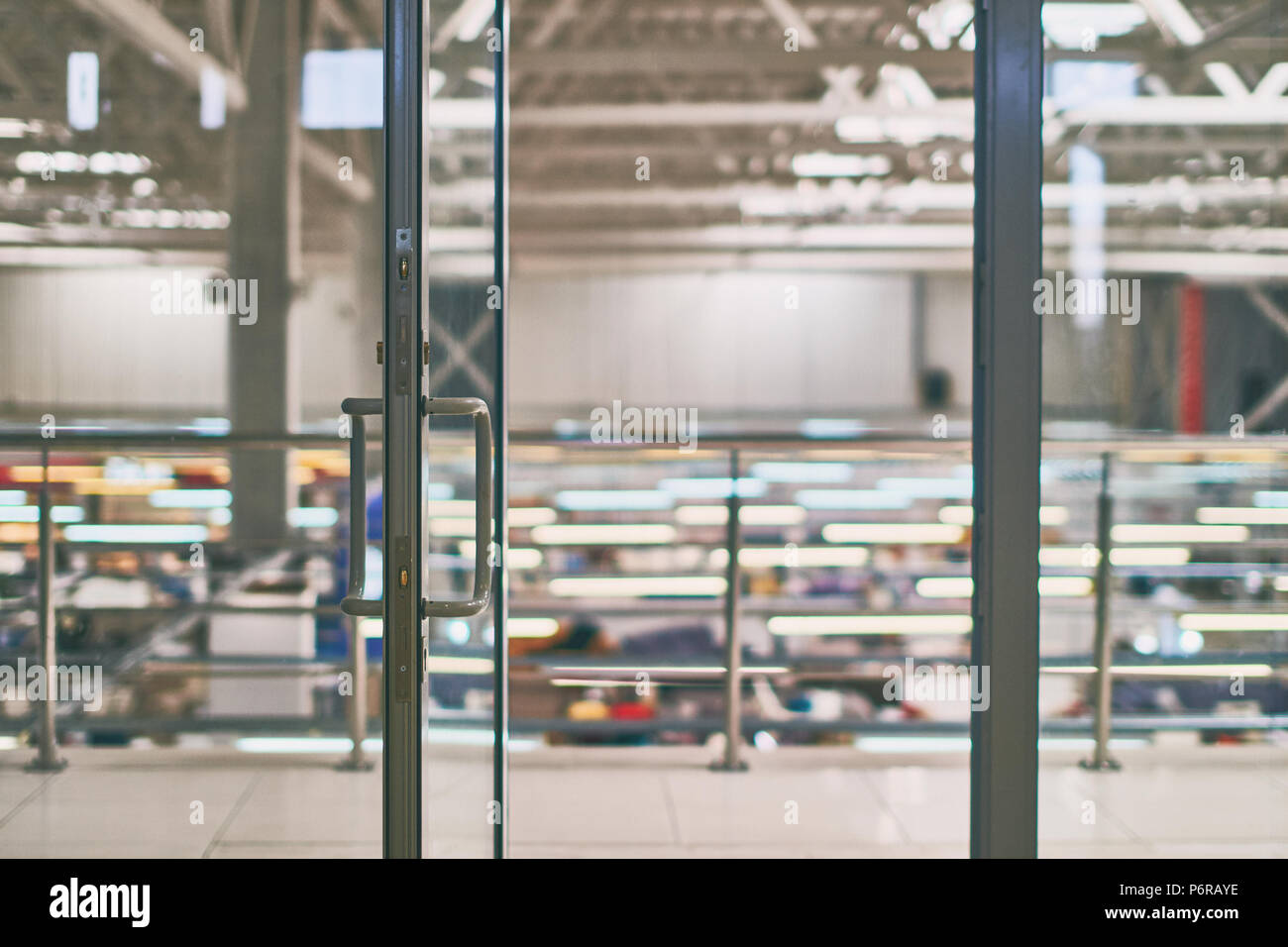 Open door in the modern office or shopping center with bokeh background - Stock Image