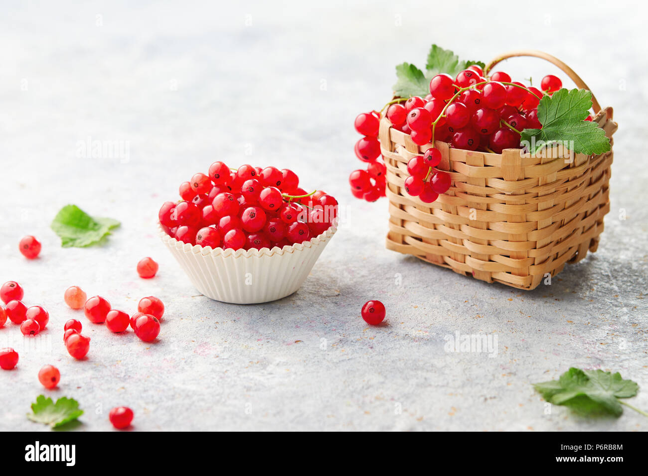 Baking cup and a little wicker basket with fresh red currants (ribes rubrum). Stock Photo