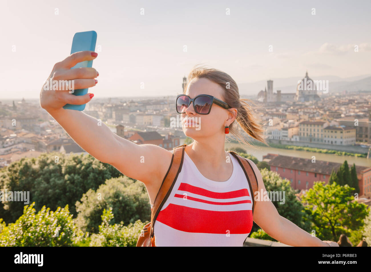 Young woman posing taking selfie with smartphone traveling in Florence, Tuscany, Italy - Stock Image