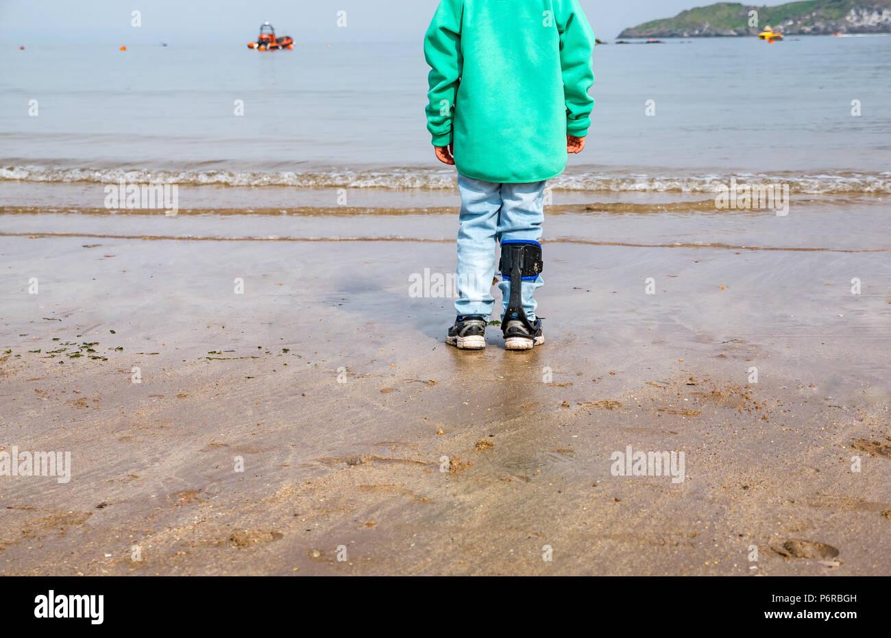 Boy with right hemiplegia wearing carbon fibre turbo drop leg brace on West beach, North Berwick, East Lothian, Scotland, UK - Stock Image