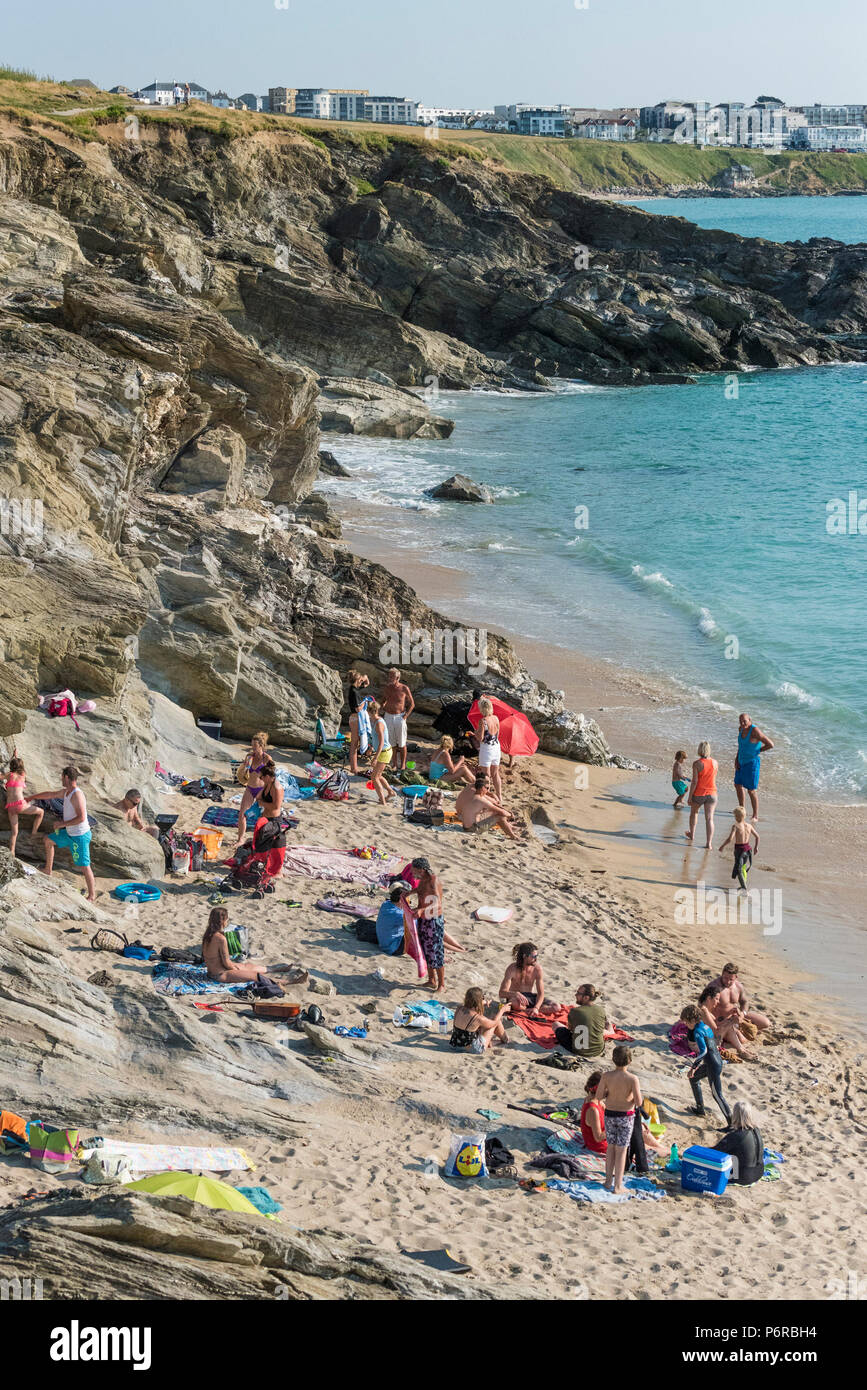 Holidaymakers enjoying the sunshine on the beach at Little Fistral in Newquay Cornwall. - Stock Image