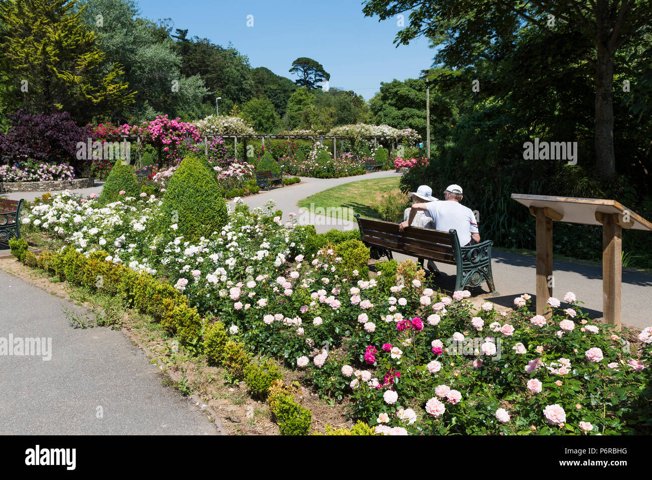Holidaymakers relaxing in the award winning Rose Garden in Trenance Park in Newquay in Cornwall. - Stock Image