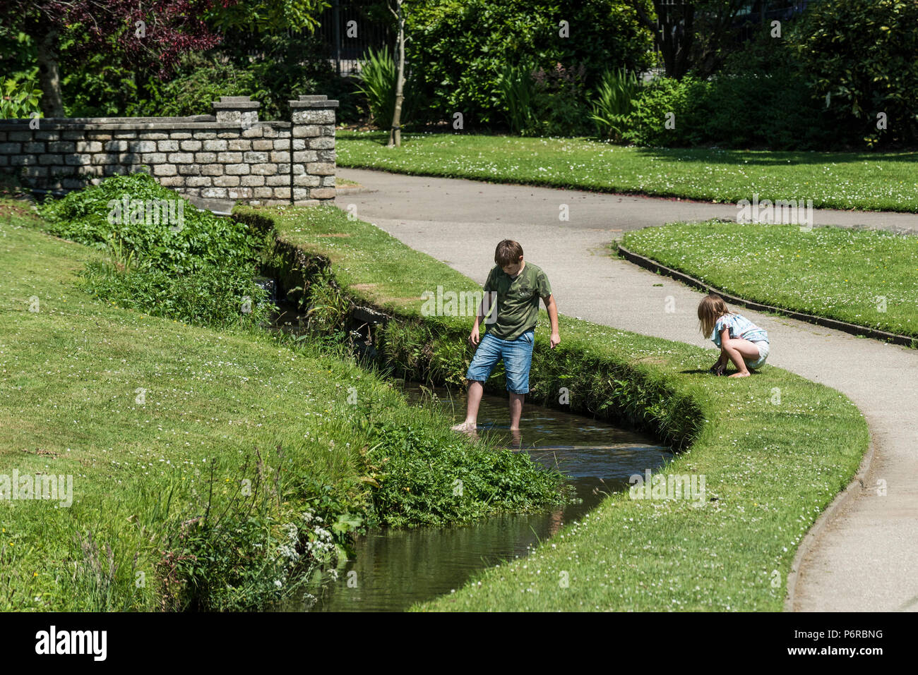 Young children playing in the stream flowing through Trenance Park in Newquay in Cornwall. - Stock Image
