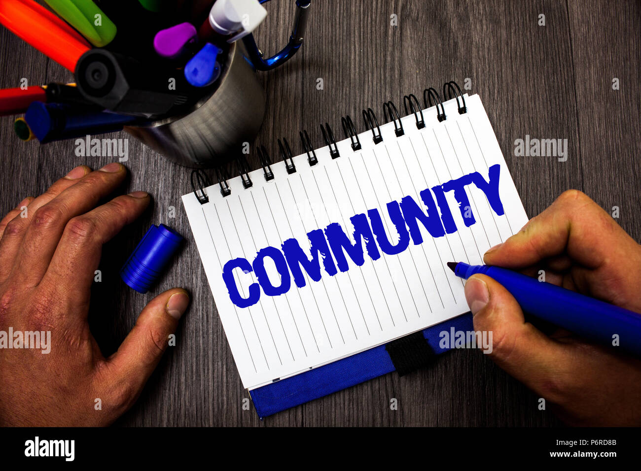 Handwriting text writing Community. Concept meaning Neighborhood Association State Affiliation Alliance Unity Group Man hold holding marker notebook i - Stock Image