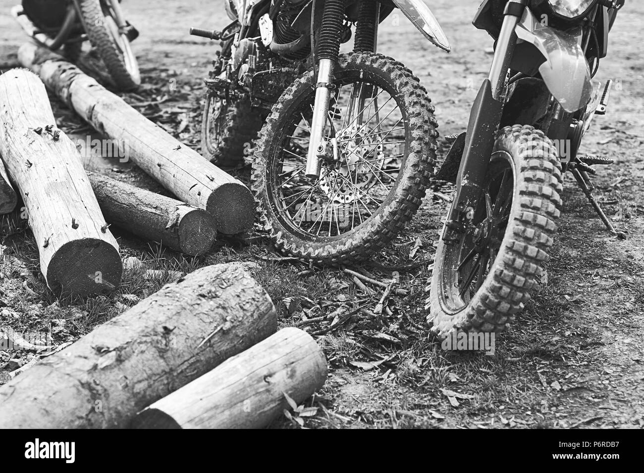 Offroad mountain motorcycles or bikes taking part in motocros competition parked on dirty terrain road with wooden logs - Stock Image