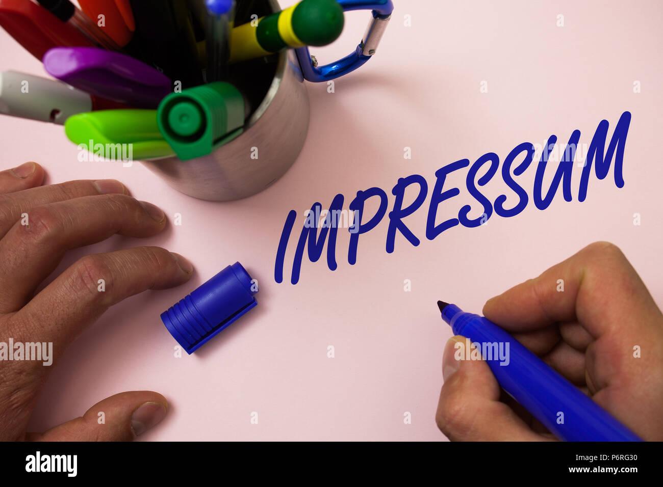 Handwriting text writing Impressum. Concept meaning Impressed Engraved Imprint German statement ownership authorship Man working inspiration holding m - Stock Image