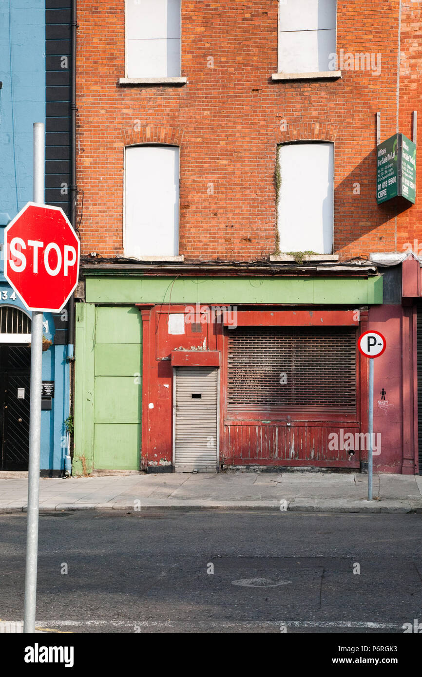 Street view of an empty building/house with windows blocked up and signs of decay yet colourful and interesting in an abstract way, Dublin, Ireland. Stock Photo