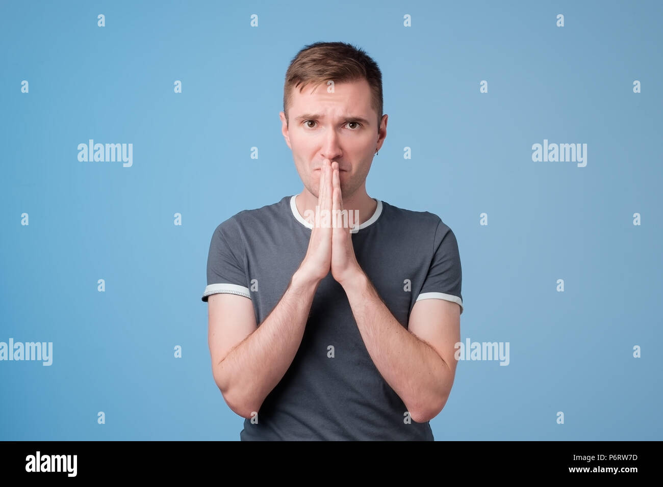 Handsome young man in blue t-shirt pressings palms together and looking at camera, begging for forgiveness - Stock Image
