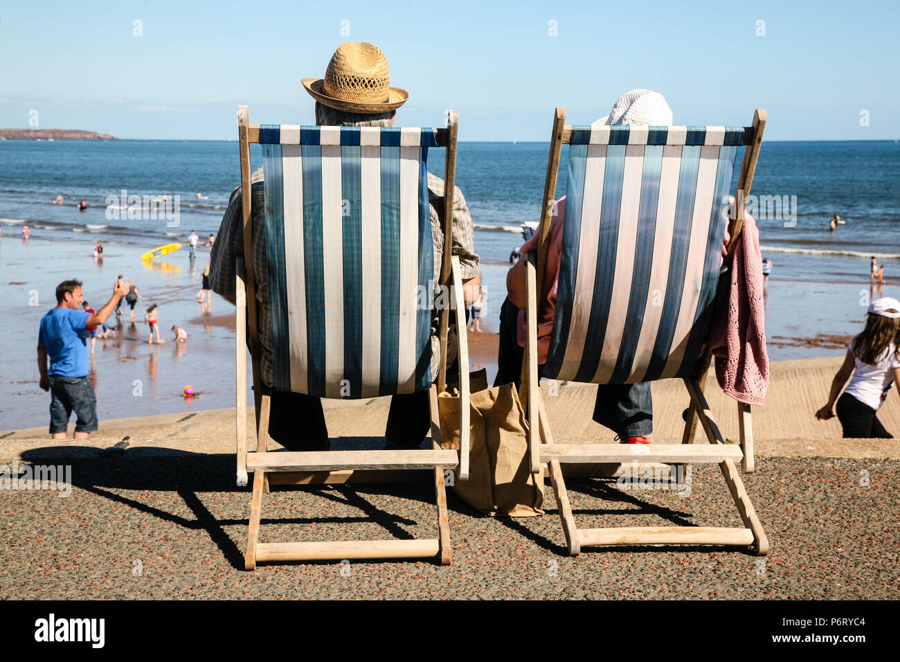 Older Hatted Couple enjoying the English Summer heatwave by the seaside in Traditional striped Deck chairs by the beach in Dawlish, England, Europe. Stock Photo