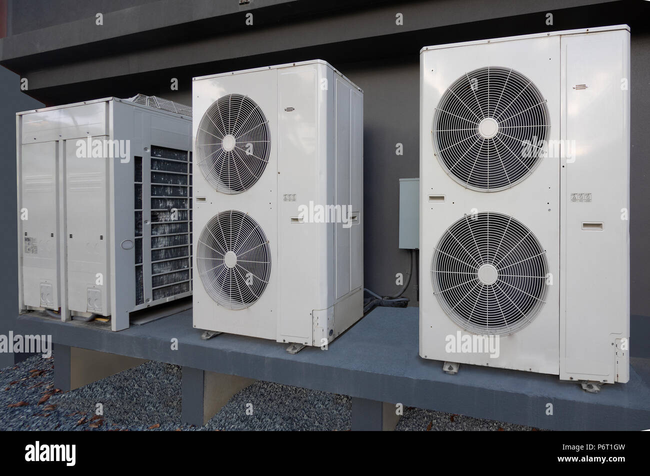 Air conditioning and heating units outside an apartment complex - Stock Image