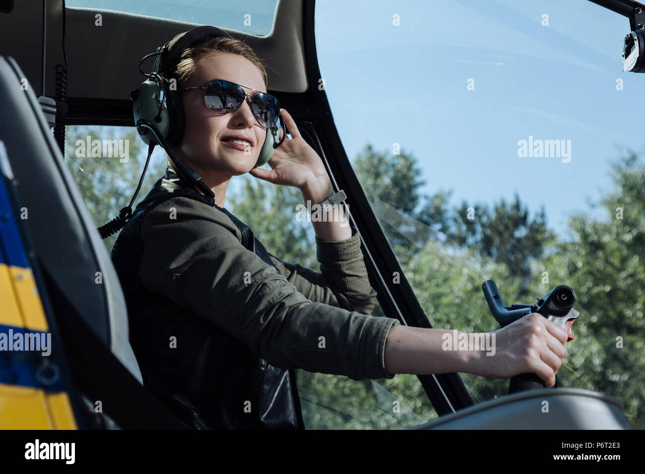 Close up of a pretty female pilot posing in helicopter - Stock Image
