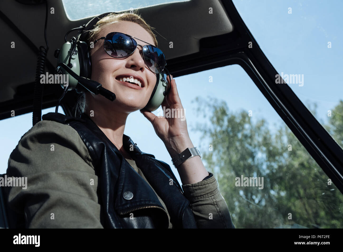 Cheerful helicopter pilot smiling while listening to air traffic controller - Stock Image