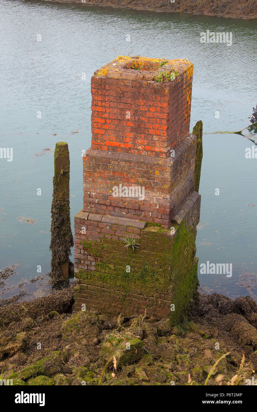 A brick built tall pillar which is either a vent or access manhole beside the river giving access to underground workings. - Stock Image