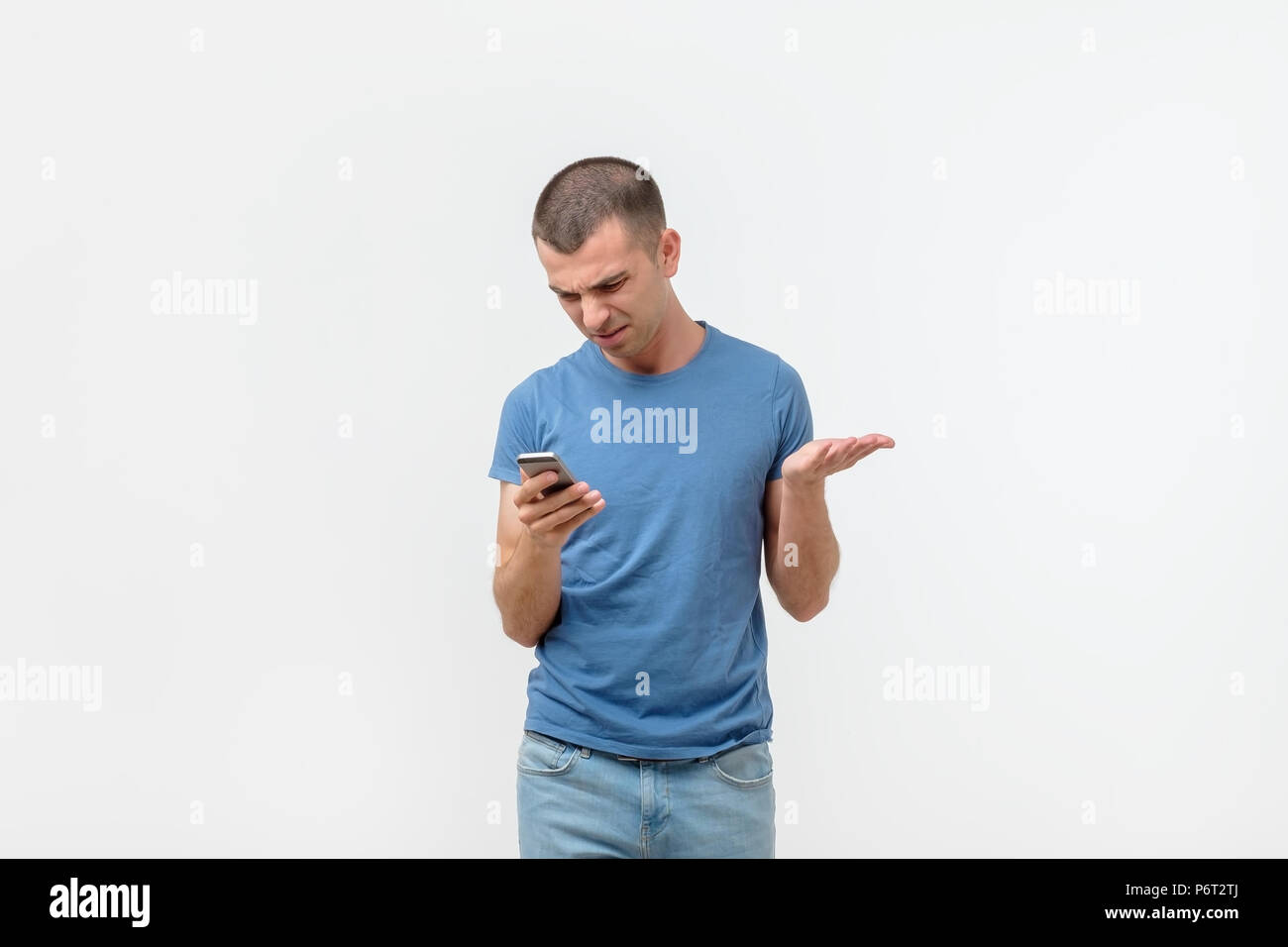Closeup worried hispanic man looking at his smart phone with anger and confusion isolated on gray wall background. Stock Photo