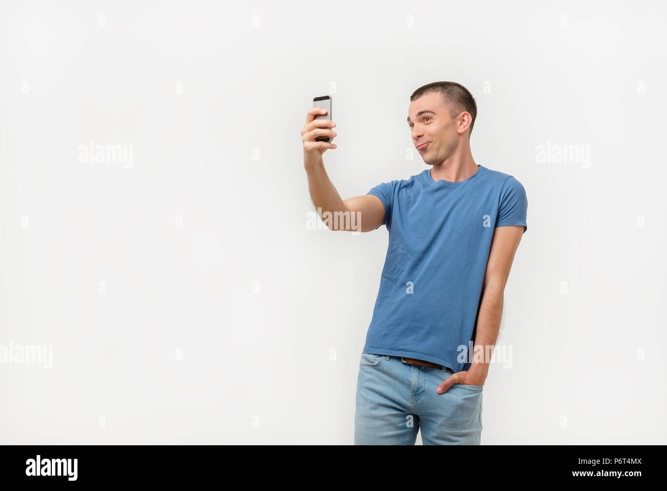 Portrait of trendy narcissistic hispanic man holding hand in pocket of pants shooting self picture. - Stock Image