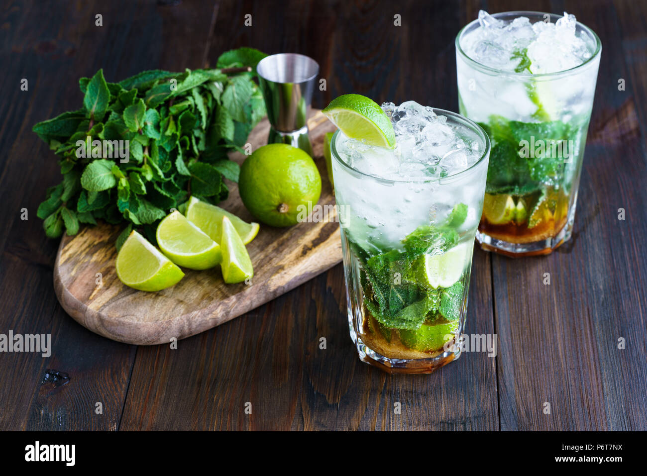 Dirty mojito and ingredients (fresh mint, sliced lime) served on a dark wooden board. High resolution. - Stock Image