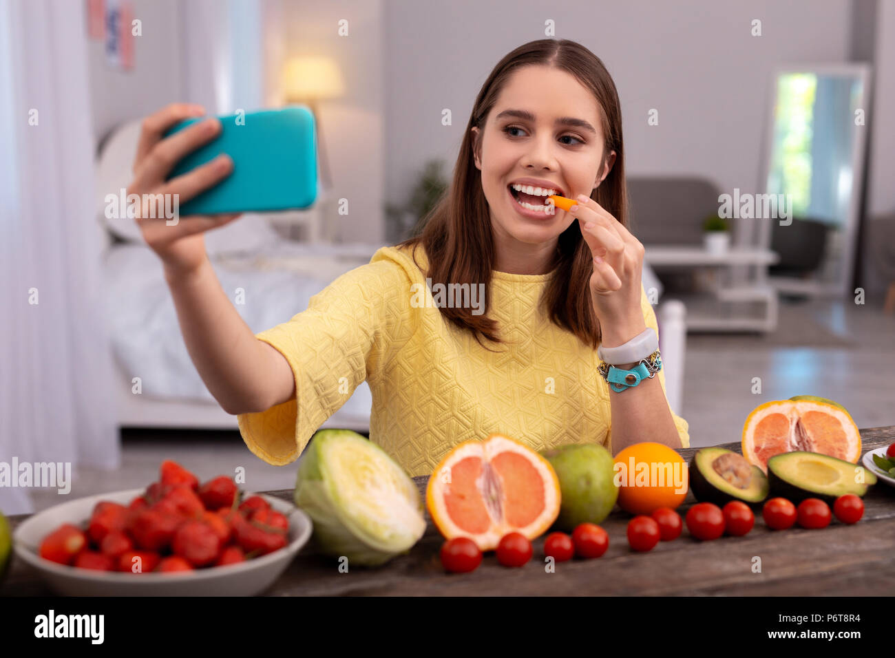 Happy teen blogger eating carrot - Stock Image