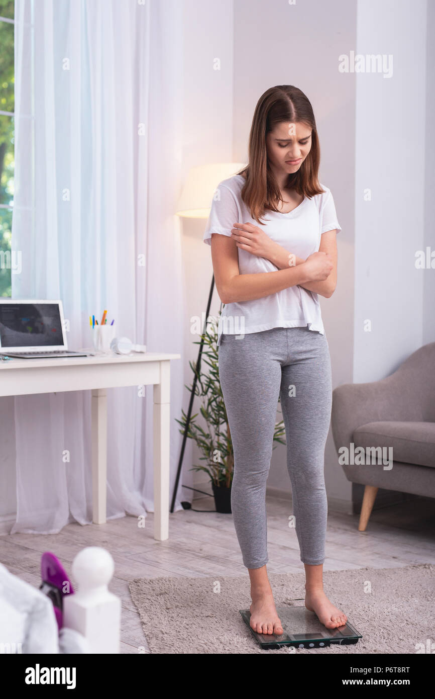 Unhappy teen girl monitoring weight - Stock Image