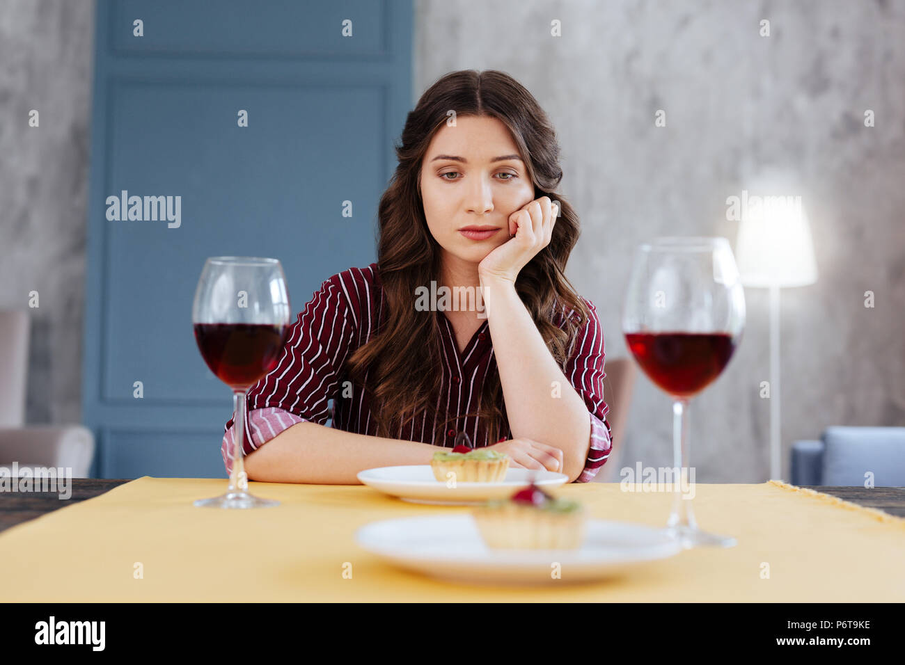 Sad woman feeling lonely waiting husband from work - Stock Image