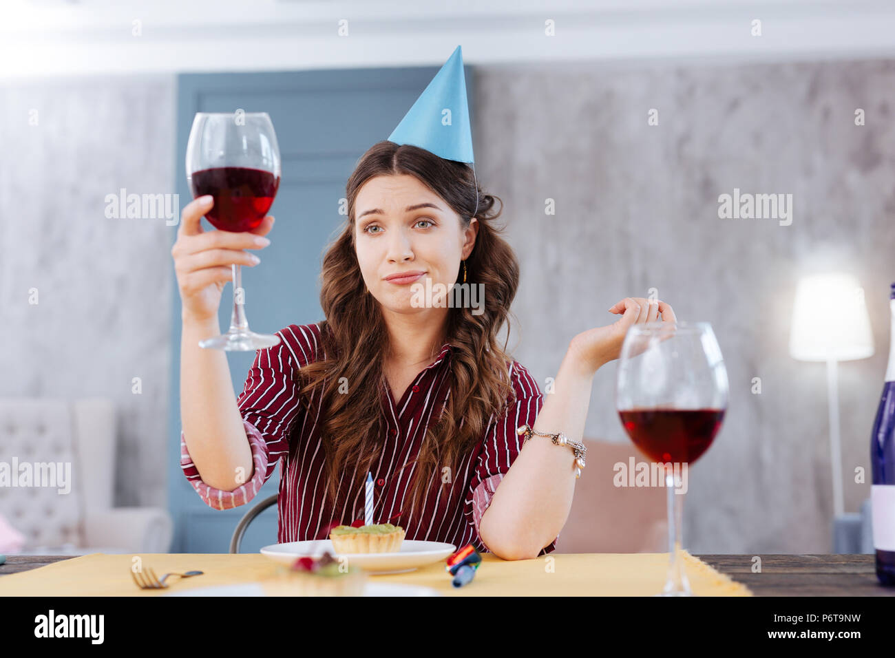 Woman making funny face while attending birthday party - Stock Image