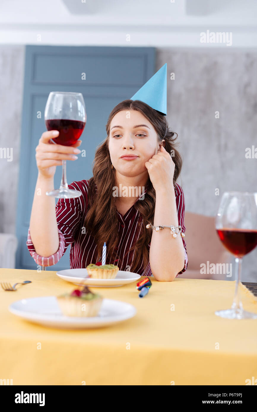 Young woman proposing a toast attending birthday party - Stock Image