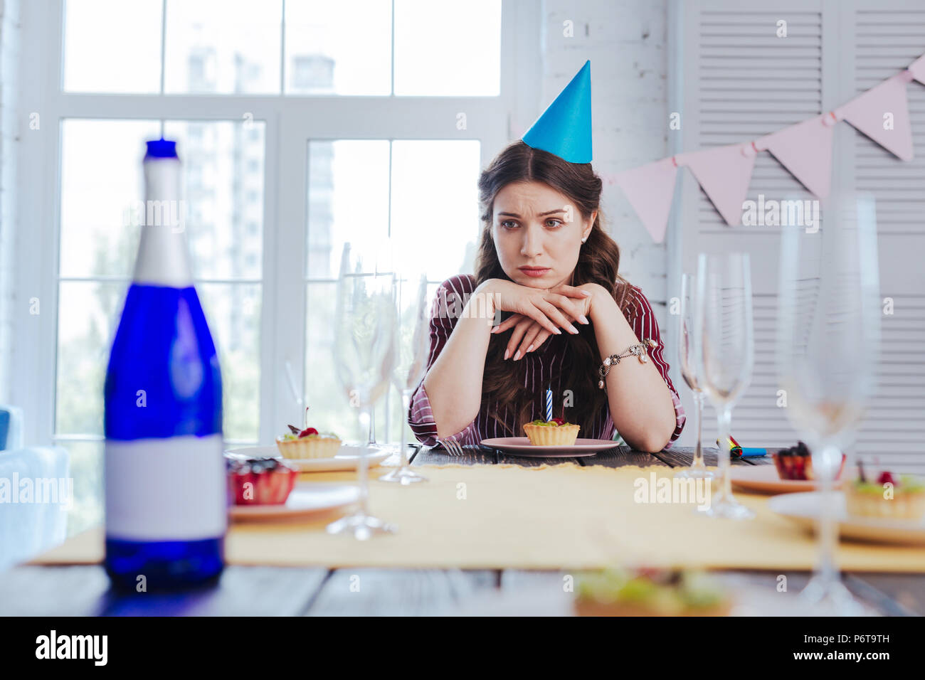 Birthday woman feeling bored waiting for her guests - Stock Image
